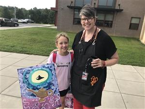 Student holds canvas standing with teacher.