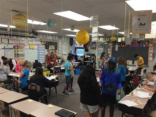 Students in a classroom with a teacher at the front.