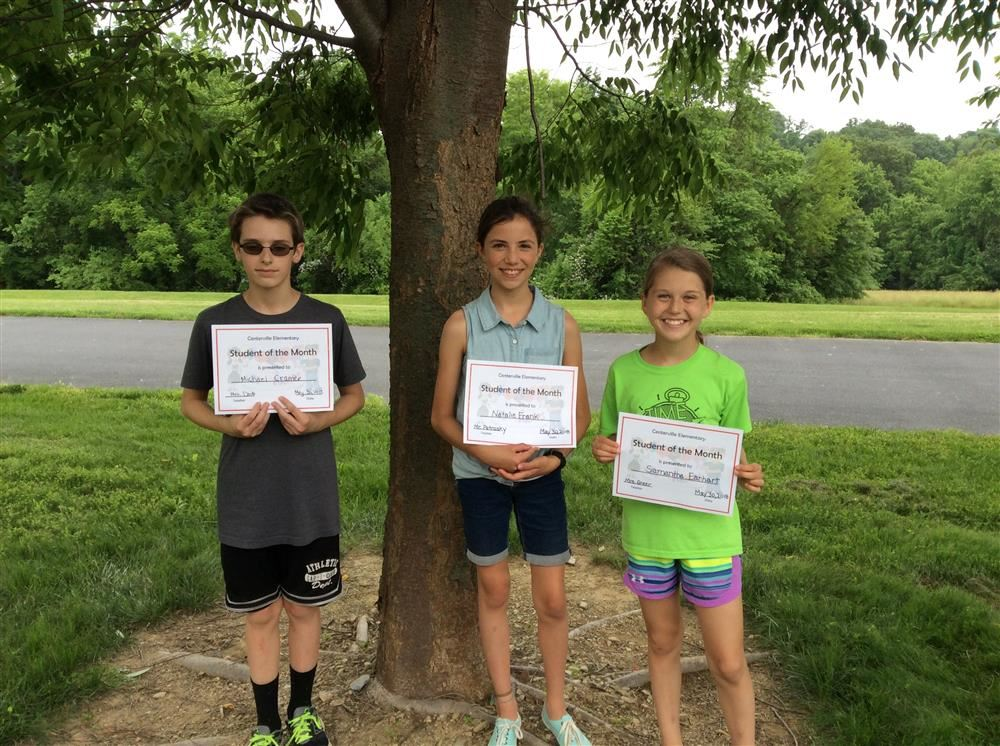 Three students stand side by side holding certificates in front of a tree.
