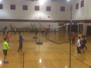 Students stand on either side of a volleyball net ready to play.