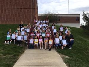 Second grade students and teachers display their completed autobiographies.