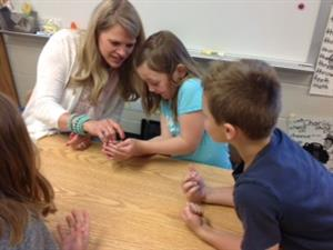 A first grade students holds a frog with the help of her teacher.