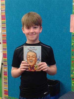 Student holds a nonfiction book about Walt Disney.