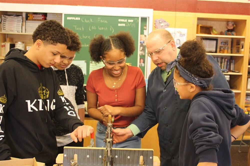 Students stand with teacher at a wood shop table.
