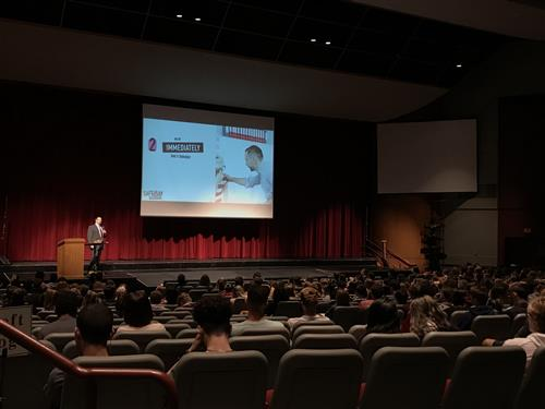 An auditorium filled with students facing a presentation and teacher with microphone speaking.