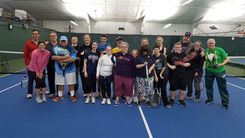 Students and volunteers stand on a tennis court holding rackets, smiling toward the camera.